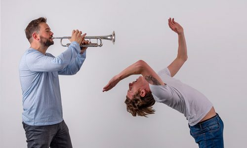 a man playing trumpet and a man dancing