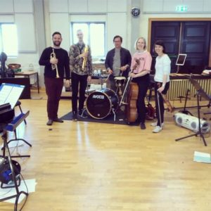 Five people standing with musical instruments in rehearsal room.